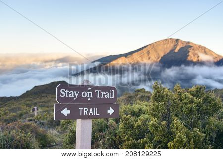 Trail with sign Stay on trail in beautiful mountains with scenic view above the clouds at sunset or sunrise
