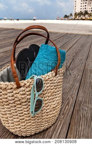 Closeup of straw bag with summer accessories on the wooden bridge at the tropical beach vacation concept