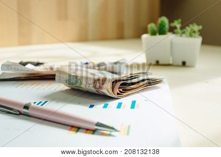 Business Equipment With Pen And Money Placed On Information Paper Has Plant In Vase Put It Aside. Wo