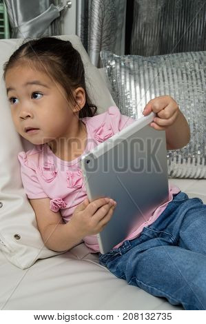 The girl is playing the tablet playfully on the couch.