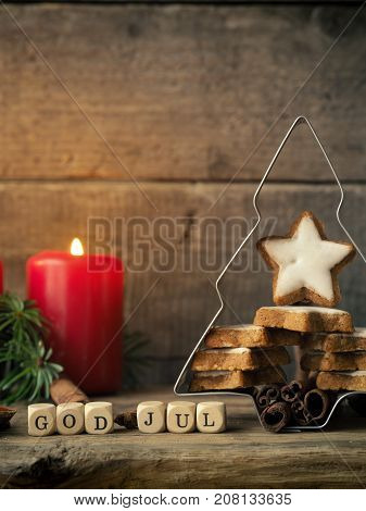 Star shaped cinnamon cookies in a tree shaped baking tin Christmas concept background