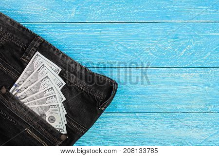 american dollar bills in jeans pocket on blue wooden background with copy space for your text. Top view.