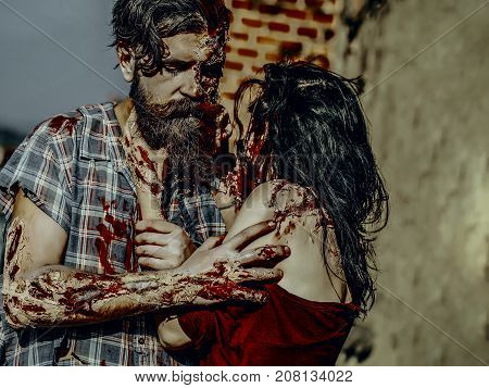 Halloween woman strangling man with bloody hands. Vampire with beard and red blood wounds outdoors. Girl with bloody brunette hair. Horror and violence. Holiday celebration concept.