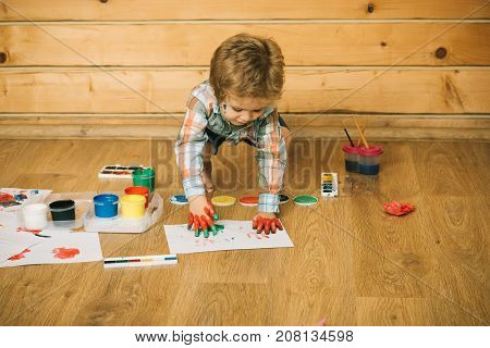 Boy Artist Drawing Handprints With Hands Colored With Paint