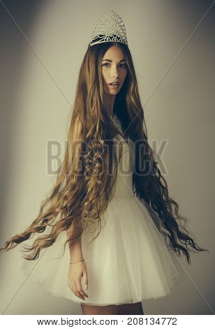 Woman with long hair white dress and crown. Beauty salon and wedding fashion. Hairdresser and cosmetics. Haircare and prom queen. Girl has fashionable makeup and healthy hair on grey background.