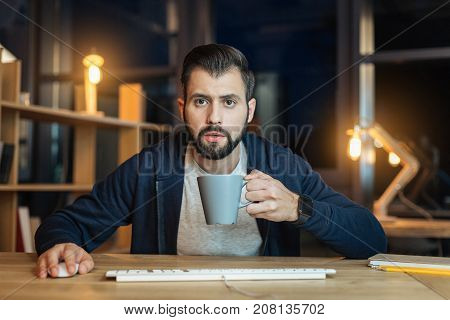 Want to have rest. Attentive male person holding mouse in right hand and having smart watches on his left arm, working late at night