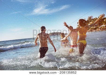 Happy friends having fun at sea beach. Space for text