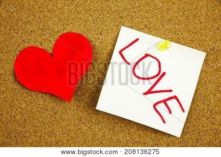A yellow sticky note writing, caption, inscription Heart with gears of love. Concept for love. Love - best medicine for heart problems. in black ext on a sticky note pinned to a cork board
