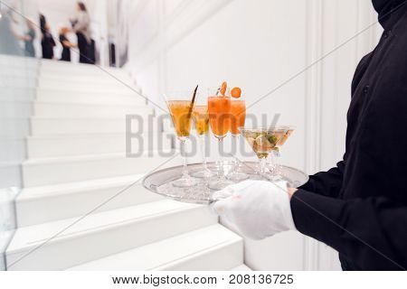 Faceless shot of server in white gloves carrying silver tray with delicious cocktails while serving party.