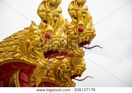The three golden serpent head or king of naga statue on white sky.