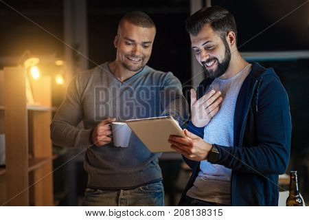 Interesting task. Cheerful male person gesticulating while standing near his colleague and looking at his gadget