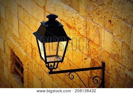 Old iron street lantern on a wall .