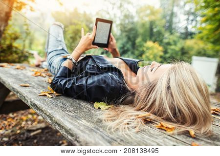 Blonde girl read ebook lying on wooden table in autumn park.