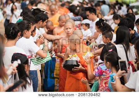 LAMPANG THAILAND - JULY 9 2017: Unidentified people offer food to monks in Devo tradition on JULY 9 2017 in Lampang Thailand. Tak Bat Devo is the tradition in end of Buddhist Lent.