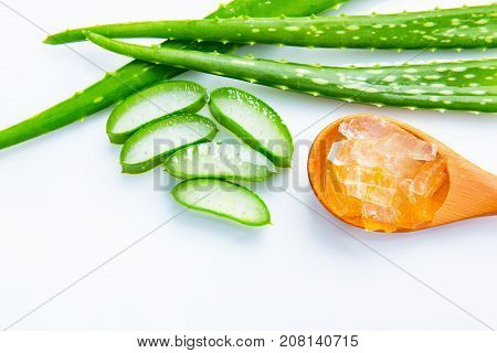 Aloe vera fresh leaves with slices and aloe vera gel on wooden spoon. isolated over white