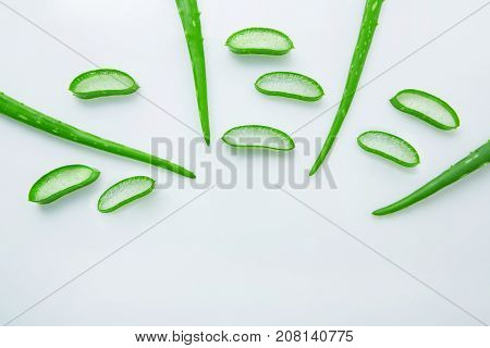 Aloe vera fresh leaves with slices aloe vera gel on wooden spoon. isolated over white
