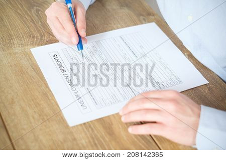 Hand filling the unemployment benefit application form