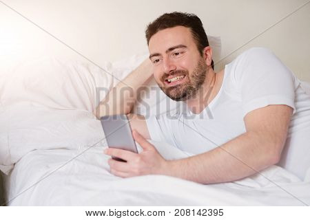 Smiling Man Using His Smart-phone Lying In Bed