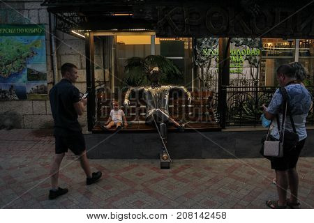 Yalta, Crimea - 11 July, People at the metal crocodile on the bench, 11 July, 2017. Night streets and embankments of the seaside city of Yalta.