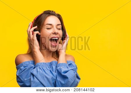Young pretty model listening to loud music with eyes closed on orange studio background.