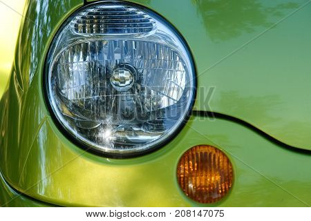 Part of car: headlamp and turn signal on green car