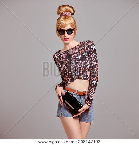 Fashion. Sexy model Girl, cheeky Emotion. Young Woman in Glamour Sunglasses, Stylish Hairstyle, fashion Autumn Outfit. Beautiful Blond Woman with Trendy Glamour Handbag Clutch, fashion pose