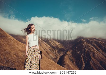 Romantic peaceful dreamy woman with closed eyes and hair wind enjoying harmony with nature. Inner peace. Happy dreamer, inspiration background. Mountain landscape. Anti-stress therapy. Life balance