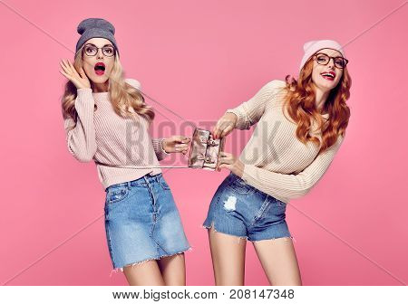 Young Woman Surprised Smiling. Having Fun Crazy. Fashion. Pretty Sisters Best Friends Twins in Stylish fashion Autumn Winter Outfit. Playful Hipster Girls. Cool Blond Redhead in Cozy Sweater on Pink