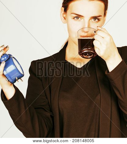 young beauty woman in business style costume waking up for work early morning on white background with clock alarm dreanking coffee close up