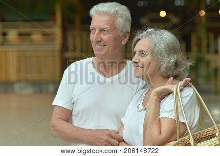 Happy senior couple standing on city street
