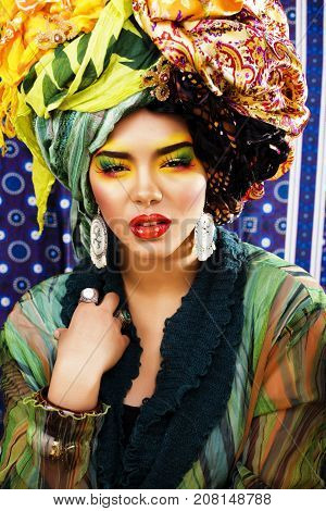 beauty bright woman with creative bright make up, many shawls on head like cubian, ethno look closeup