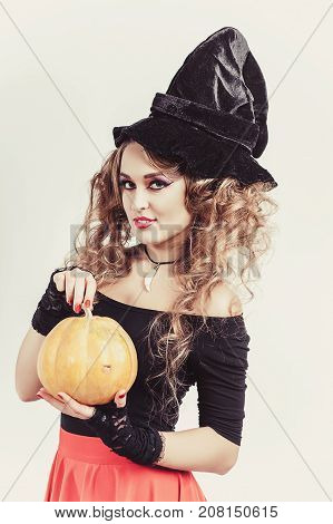 Portrait of woman holding in hands orange pumpkin isolated on gray background. Wearing black witch hat, blouse and red skirt. Vertical shot