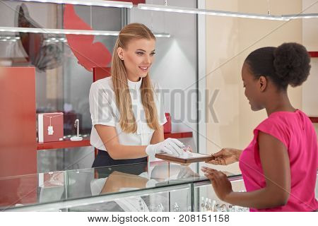 Professional jeweler helping her female customer choosing jewelry at the store.