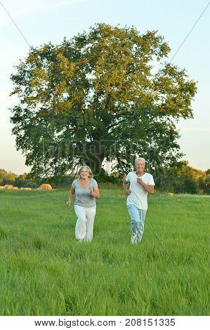 portrait of beautiful caucasian senior couple running in field
