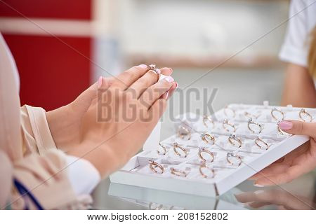 Cropped close up of a woman trying on an engagement ring at the jewelry store.