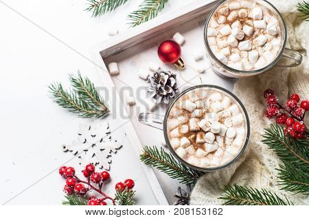 Christmas hot chocolate or cocoa with marshmallow on white with christmas decorations. Top view with copy space.