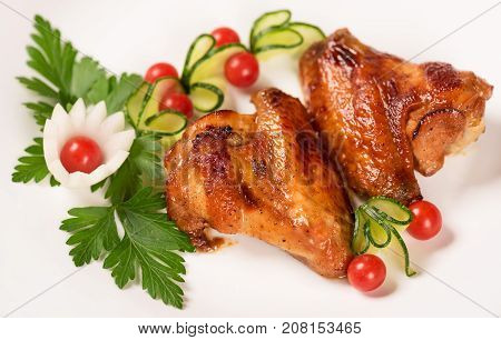 Baked chicken wings with fresh vegetables over white plate background