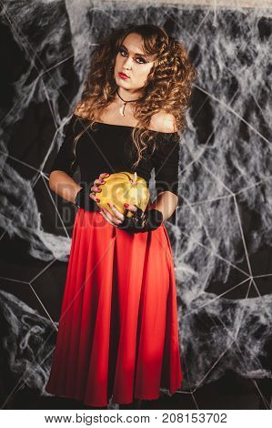 Beautifull woman in a witch's costume is holding pumpkin in front of black wall with spider net. Full lenght shot