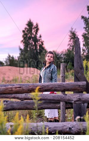 Late sunset at the countryside and cowgirl near a old wooden fence