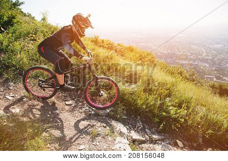 In summer on a sunny day, Ryder in a helmet rides down the gravel path from the mountainside on a mountain bike against the backdrop of a city in the distance. Extreme in caucasian city