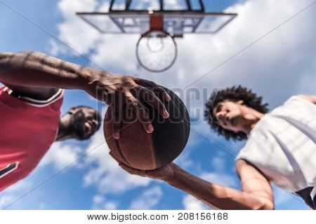 Bottom view of handsome basketball players playing on basketball court outdoors