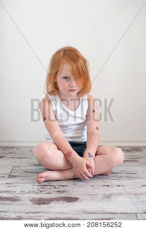 Upset redhead girl in a tattoo on the floor