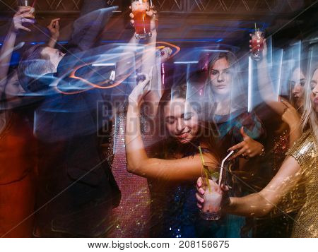 Celebration party with alcoholic drinks at night club in blurred motion. Happy friends at Christmas discotheque, active New Year company, modern youth life