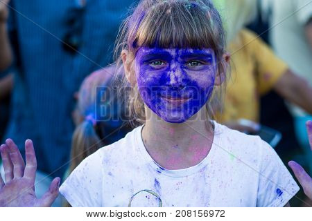 The face of a little girl in blue holi paints. Close up portrait of happy little girl on holi color festival