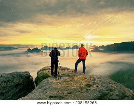 Photographer  With Eye At Viewfinder Of Camera On Tripod Stay On Cliff And Takes Photos, Talk Friend
