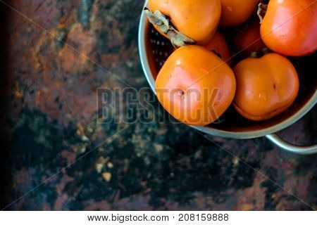 Group of persimmons in metal collander over rustic surface