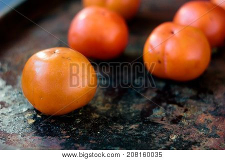 Group of persimmons on black rustic surface