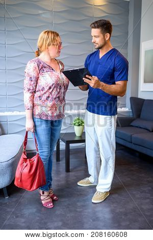 A handsome male Doctor discussing details of a medical procedure with the Patient