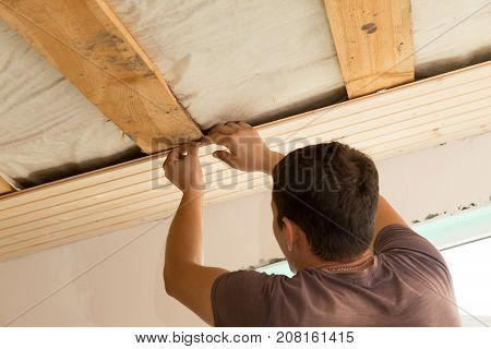 worker working on a wooden ceiling in the house .