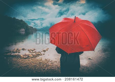 Woman with red umbrella contemplates on rain in front of a lake. Sad and lonely female person looking into distance. Grunge editing with dirt noise splotches and dust.